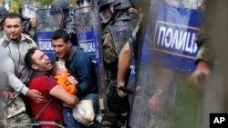 Các di dân giúp người đàn ông giữ một cậu bé bị kẹt giữa cảnh sát chống bạo động Macedonia trong vụ đụng độ hôm 21/8/2015.