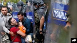 Fellow migrants help a man and boy pressured by Macedonian riot police at the border near Idomeni, northern Greece, Aug. 21, 2015. Migrants hope to cross into Macedonia, which has declared a state of emergency because of the immigrant influx.