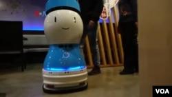Robot pelayan menyambut tamu dan mengantar makanan di restoran. (Foto: VOA)