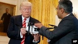 "George Mathew, CEO of Kespry, shows a drone to President Donald Trump during the ""American Leadership in Emerging Technology"" event in the East Room of the White House, June 22, 2017, in Washington."