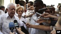 Former President Jimmy Carter, left, speaks with journalists as his wife Rosalynn looks on after visiting the Belen convent in Old Havana, Cuba, March 29, 2011