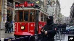A tram drives past a Turkish police officer as he patrols central Istanbul's Istiklal Avenue, the main shopping road of Istanbul, Jan. 5, 2017.