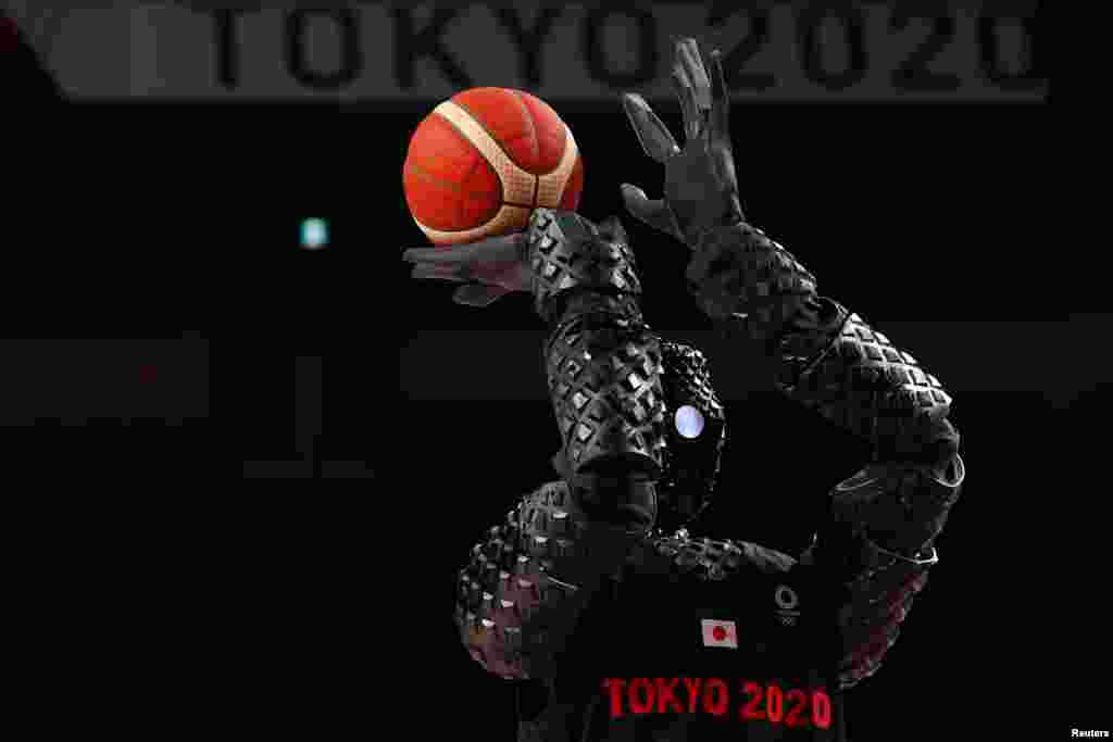 A Japanese basketball robot shoots the ball during half time of the women's game between Belgium and Puerto Rico during the Tokyo 2020 Olympics at Saitama Super Arena, in Saitama, Japan.