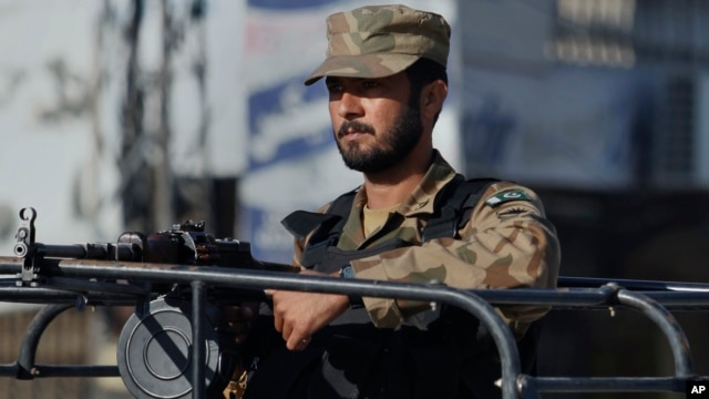 FILE - A Pakistan army soldier mans at a vehicle during a curfew in Rawalpindi, Pakistan on Saturday, Nov. 16, 2013.