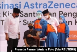 Seorang santri Pesantren Lirboyo sedang disuntik vaksin COVID-19 buatan AstraZeneca, di Kediri, Jawa Timur, 23 Maret 2021. (Foto: Prasetia Fauzani/Antara Foto via Reuters)