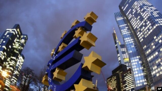 The Euro sculpture stands in front of the European Central Bank, right, in Frankfurt, Germany, December 16, 2011.