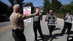 El sub jefe de la oficina del Sheriff del Conado de Los Ángeles pide a manifestantes que permanezcan en la acera frente al Laboratorio de Propulsión a Chorro de la NASA antes de la visita del vicepresidnete Mike Pence el sábado, 28 de abril, de 2018.