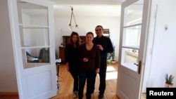 Jozef Walukiewicz, his wife Anna and daughter Katarzyna stand inside their renovated house in the village of Rosow, Germany, located near the Polish border, April 7, 2013.