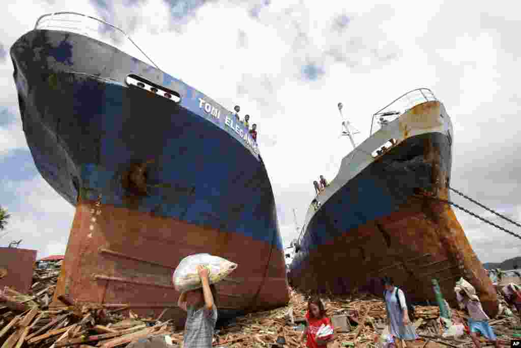 Survivors pass by two large boats that were washed ashore by strong waves caused by Typhoon Haiyan in Tacloban city, Leyte province, central Philippines, Nov. 10, 2013.