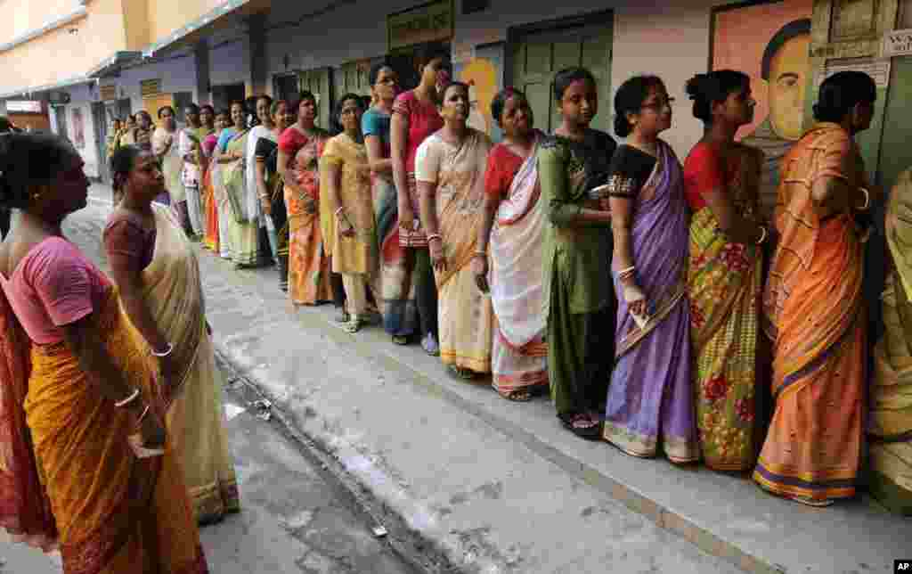 Women stand in line to cast their votes at a polling booth in Howrah district, on the outskirts of Kolkata, April 30, 2014.