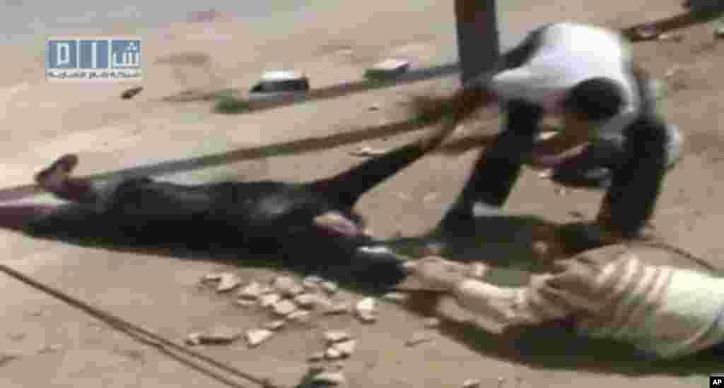 Amateur video image shot on April 24, 2011 and made available by SHAAM News Network and posted on Youtube, May 12, 2011, shows two men crawling close to the ground and dragging a woman to safety in Daraa, Syria. (AP image)