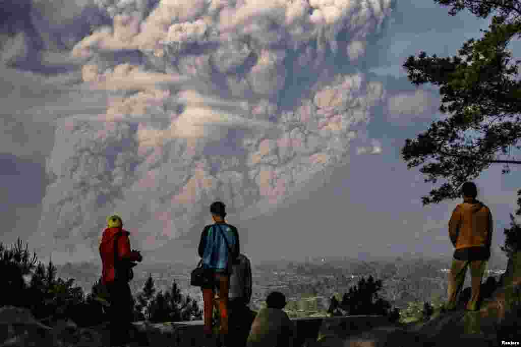 People watch as Mt. Sinabung ejects ash into the air during an eruption in Karo regency, Indonesia's North Sumatra province in this photo taken by Antara Foto.