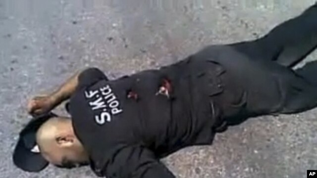 This undated amateur video image posted on the internet and shown on Syrian state television shows a Syrian policeman lying on the ground apparently dead from gunshot wounds in Jisr al-Shughour, northern Syria. (AP cannot independently verify the location