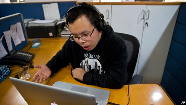 FILE - Chinese journalist Li Xin talks to an Associated Press reporter over Skype, at the AP office in New Delhi, India, Nov. 20, 2015.