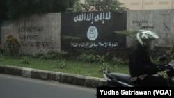 Simbol Negara Islam (ISIS) dan tulisan bernada dukungan di Solo, Jawa Tengah, sebelum dihapus oleh pemerintah setempat, Agustus 2014.