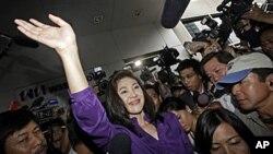 លោកស្រី Yingluck Shinawatra មេដឹកនាំគណបក្សភឿថៃដែលបានទទួលជ័យជំនះក្នុងការបោះឆ្នោតនៅប្រទេសថៃកាលពីថ្ងៃអាទិត្យបោយដៃទៅអ្នកគាំទ្រ។