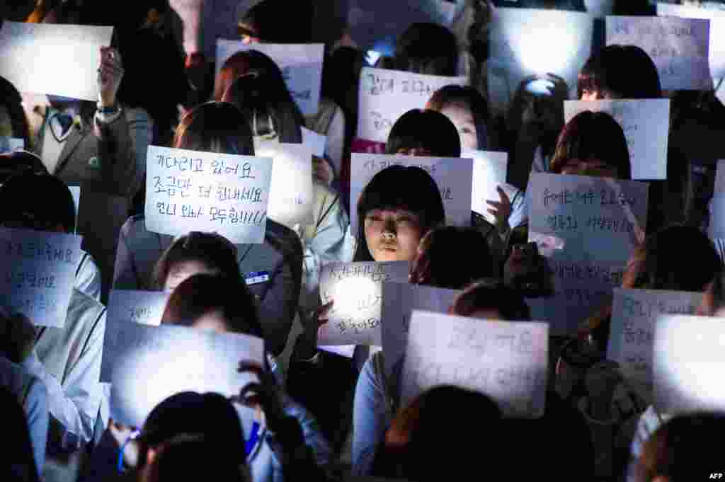 Students at Danwon High School in Ansan hold messages for missing schoolchildren who are among the unaccounted for passengers trapped in a South Korean capsized ferry.