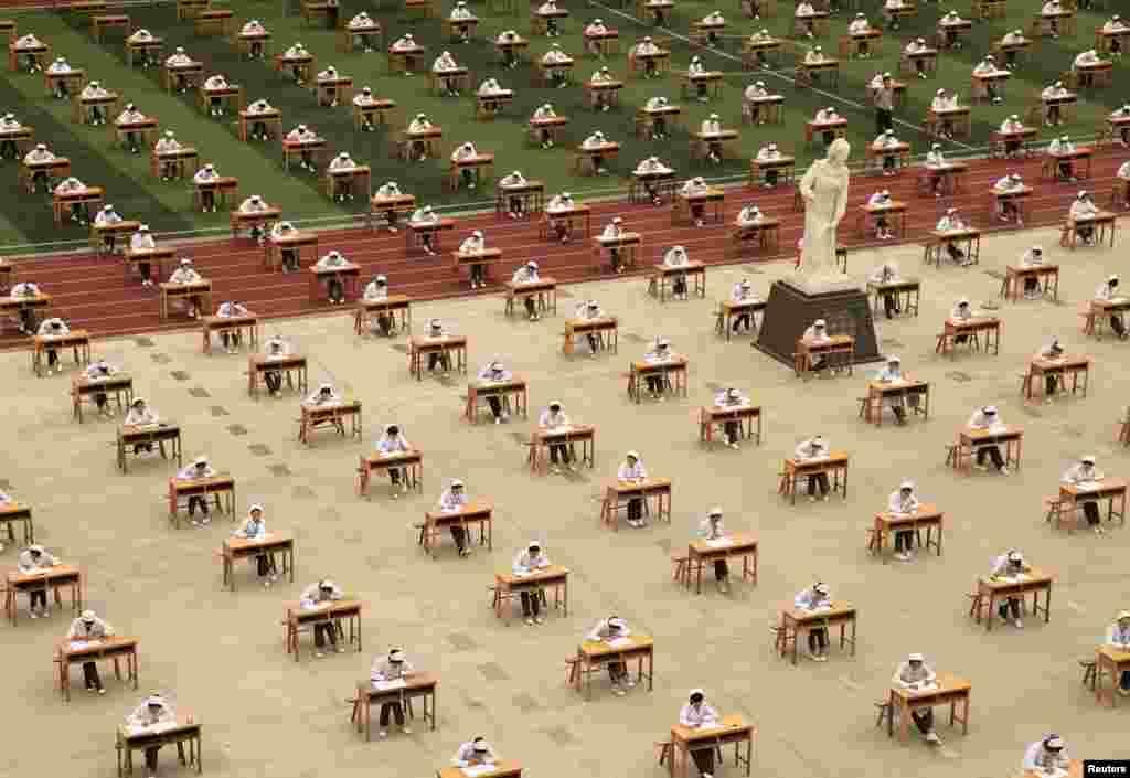 Hàng trăm sinh viên của trường điều dưỡng tham gia một kỳ thi ngoài trời trong một sân chơi của một trường dạy nghề tại thành phố Bảo Kê, tỉnh Thiểm Tây, Trung Quốc.