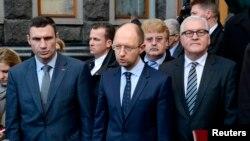 Menteri Luar Negeri Jerman Frank-Walter Steinmeier (kanan) bersama pemimpin oposisi Ukraina Vitaly Klitschko (kiri) dan Arseny Yatsenyuk setelah penandatanganan perjanjian damai dengan Presiden Viktor Yanukovych (21/2). (Reuters/Maks Levin)