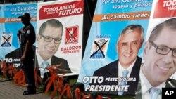 ເຈົ້າໜ້າທີ່ຮັກສາຄວາມປອດໄພເອກະຊົນຄົນນຶ່ງຢືນຍາມຢູ່ຕໍ່ໜ້າ ປ້າຍໂຄສະນາຫາສຽງເລືອກຕັ້ງຂອງທ່ານ Perez Molina, ຜູ້ສະມັດປະທານາທິບໍດີສັງກົດພັດຮັກຊາດ ແລະທ່ານ Manuel Baldizon, ຜູ້ສະມັກແຂ່ງຂັນປະທານາທິບໍດີສັງກັດພັກFreedom Revival party ໃນນະຄອນ Guatemala City, ກົວເຕມາລາ.