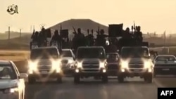 FILE - An image grab taken from a different video, released by the Islamic State group's official Al-Raqqa site via YouTube, allegedly shows IS recruits riding in trucks in an unknown location.