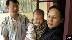 Taiwanese security guard Huang Chin-tsai, 44, looks at his his wife, Vu Thi Minh, 30, from Vietnam and their six-month-old daughter in their home, in Wanli, 30 miles north of Taipei, Taiwan, March 1, 2003.