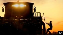 Un granjero sube a su máquina cosechadora de maíz en Pleasant Plains, Illinois.