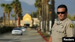 FILE - A police officer is seen standing guard at a mosque in California.