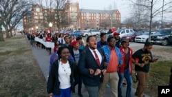 Mahasiswa Universitas Oklahoma(10/3) berbaris menuju asrama Sigma Alpha Epsilon di Norman, Oklahoma, yang kini ditutup (AP Photo/Sue Ogrocki).