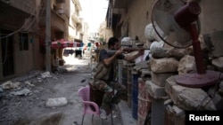 A Free Syrian Army fighter points his weapon as he takes up position behind sandbags in Deir al-Zor, Syria, July 13, 2013.