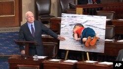 Thượng nghị sĩ John McCain đứng cạnh tấm ảnh phóng lớn xác một em bé Syria 3 tuổi trôi dạt vào bãi biển. Ông hối thúc Hoa Kỳ giúp đỡ người tị nạn Syria tốt hơn nữa.