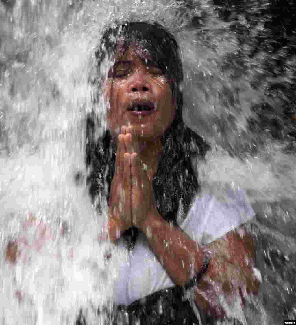 "A Balinese Hindu devotee bathes in the Sebatu waterfall during a ""Melukat"" purification ritual in Gianyar District in Bali, Indonesia."