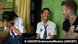 ທູດສັນຖະວະໄມຕີ ອົງການ UNICEF ທ້າວ ເດວິດ ເບັກແຮັມ (David Beckham) ຍິ້ມກັບນາງ ສຣີປຸນ (Sripun) ອາຍຸ 15 ປີ, ຊ້າຍ ກັບໝູ່ຂອງລາວ ທ້າວ ເອໂກ, ກາງ, ໃນເມືອງ ເຊມາຣັງ, ອິນໂດເນເຊຍ. 27 ມີນາ, 2018.