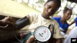 FILE - A nurse trainee measures a pregnant woman's blood pressure during a prenatal consultation at the United Brethren in Christ Hospital in the town of Mattru Jong, Bonthe District, Sierra Leone.