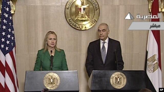 Hình ảnh Bộ trưởng ngoại giao Ai Cập Mohammed Kamel Amr đưa ra loan báo ngưng bắn tại Cairo và Ngoại trưởng Hoa Kỳ Hillary Clinton trên truyền hình quốc gia Ai Cập.