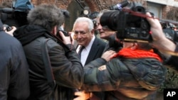 Former International Monetary Fund chief Dominique Strauss-Kahn is surrounded by photographers as he leaves for court for his trial on sex offense charges, including the alleged procurement of prostitutes, in Lille, France, Feb. 17, 2015.