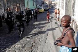 A boy looks at police officers on patrol in the Morro da Providencia slum in Rio de Janeiro, April 26, 2010.