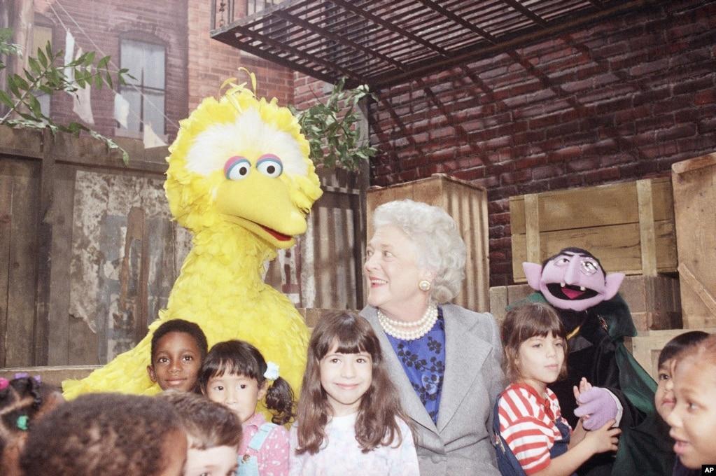 1989年10月19日,美國總統喬治·W·布什(小布什)的母親芭芭拉·布什和兒童們與電視卡通片《芝麻街》裡的角色大鳥合影。