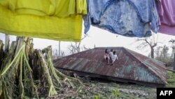 Anak-anak duduk di atas atap rumah yang diterbangkan topan Koppu di kota Casiguran, provinsi Auroran, sebelah timur laut Manila, Filipina (21/10). (AFP/Dante Diosina)