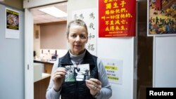 Karen Short, wife of Australian missionary John Short, poses with a photo of her husband inside the Christian Book Room in Hong Kong, Feb. 20, 2014.