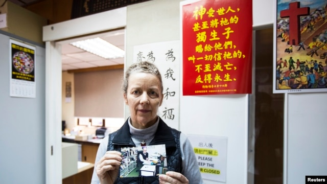 Karen Short, wife of Australian missionary John Short, poses with a photo of her husband inside the Christian Book Room in Hong Kong, Feb. 20, 2014. (Reuters)