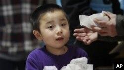 从福岛核电站附近地区撤出的男孩手持分发的食物
