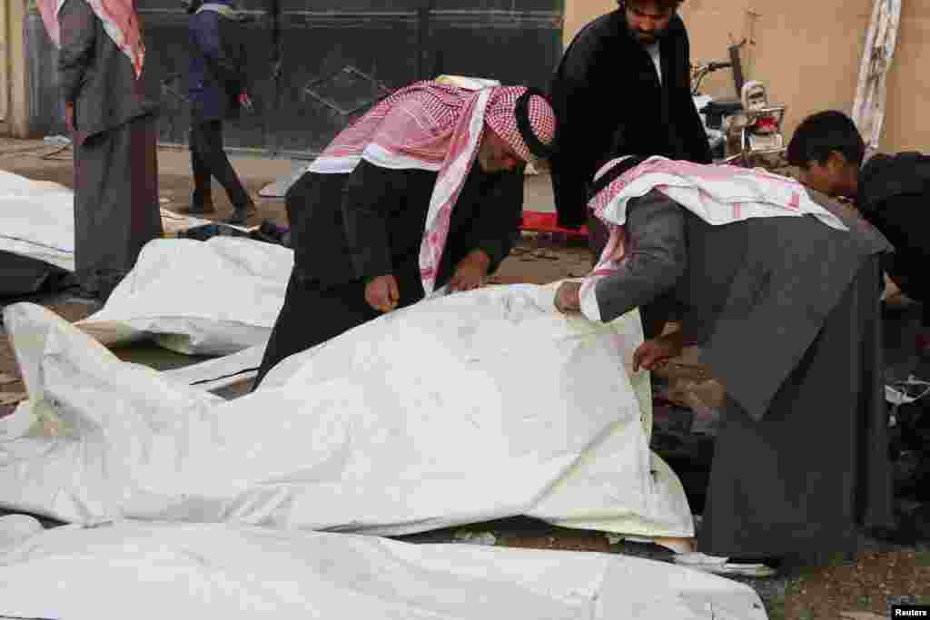 People attempt to identify bodies at a hospital, after what activists said were airstrikes by forces loyal to President Bashar al-Assad, in Raqqa, Syria, Nov. 25, 2014.