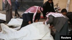 Warga berusaha mengidentifikasi jenazah di rumah sakit menyusul serangan udara oleh pasukan Suriah di Raqqa (25/11). (Reuters/Nour Fourat)