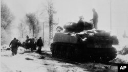 FILE - U.S. tanks move in the snow and ice from the town of Tri-le-Cheslaing, Belgium, on Jan. 7, 1945 during the Battle of the Bulge in World War II. Robbie Edmonds, taken prisoner during the battle, refused to separate Jewish POWs from the other America