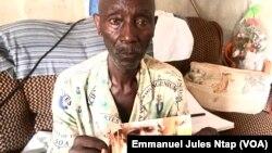 Albert Kouawa, tenant la photo de son fils Frenzo porté disparu depuis 2015 à Yaoundé, le 31 août 2020. (VOA/Emmanuel Jules Ntap)
