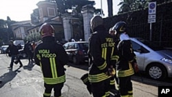 Italian firefighters stand in front of the Swiss Embassy in Rome where a parcel bomb exploded, 23 Dec 2010