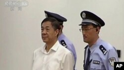 In this image taken from video, disgraced politician Bo Xilai, center, enters the courtroom, flanked by police guards at Jinan Intermediate People's Court in eastern China's Shandong province, Aug. 22, 2013.