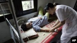 Una enfermera atiende a un paciente de dengue.