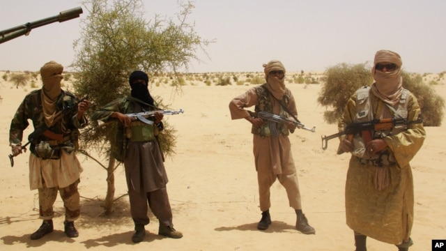 Ansar Dine fighters stand guard during hostage handover, outside Timbuktu, Mali, April 24, 2012.